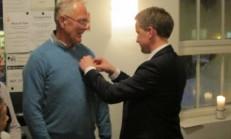 Varaordfører Jørgen Kristiansen fester fortjenestemedaljen på Harald Båslands bryst.